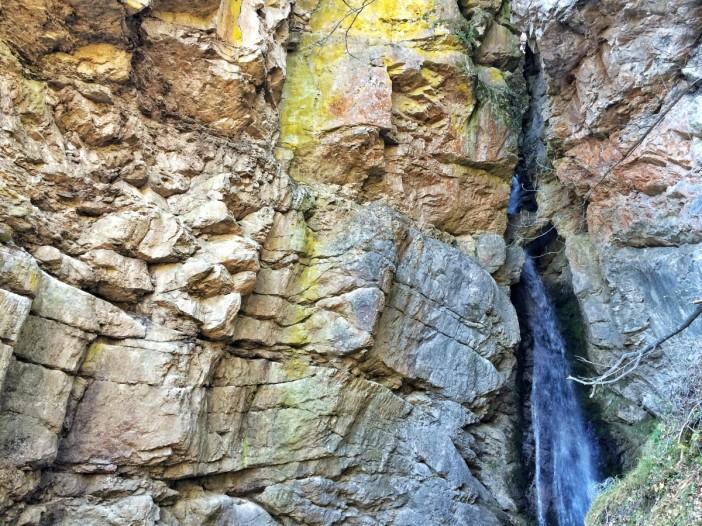Ein Wasserfall zwängt sich durch eine kaum erkennbare Schlucht.