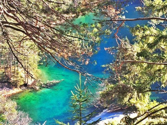 Türkis und blau schimmert der Fernsteinsee durch das Gehölz. Hinauf zur Via Claudia, die hoch über der Fernstraße zur Passhöhe führt.