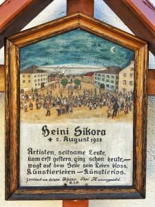 Ein gemaltes Kreuz steht an der Nordseite der Pfarrkirche in Imst. Da wird eines Mannes gedacht, der offenbar bei einem Hochseilakt am heutigen Stadtplatz tödlich verunglückte.