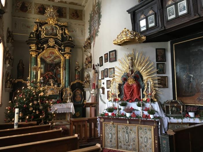 Innenansicht der Thierbergkapelle mit der Muttergottesfigur und dem Altargemälde, das die Enthauptung Johannes des Täufers thematisiert.